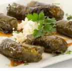 Stuffed grape leaves with basmati rice and herbs topped with homemade pomegranate sauce