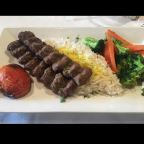 Two skewers of grilled marinated fresh ground beef, served with saffon, basmati rice, grilled tomato and vegetables